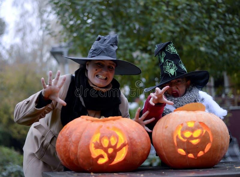 Halloween-pompoenen en twee heksen stock foto's