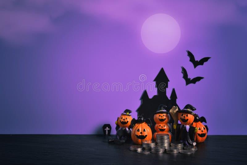 Halloween-pompoenen hefboom-o-lantaarn met de stapel groeiende zaken van het geldmuntstuk op donkere purpere achtergrond stock foto