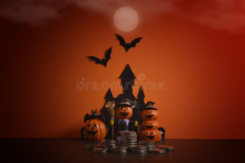 Halloween-pompoenen hefboom-o-lantaarn met de stapel groeiende zaken van het geldmuntstuk op donkeroranje achtergrond royalty-vrije stock foto