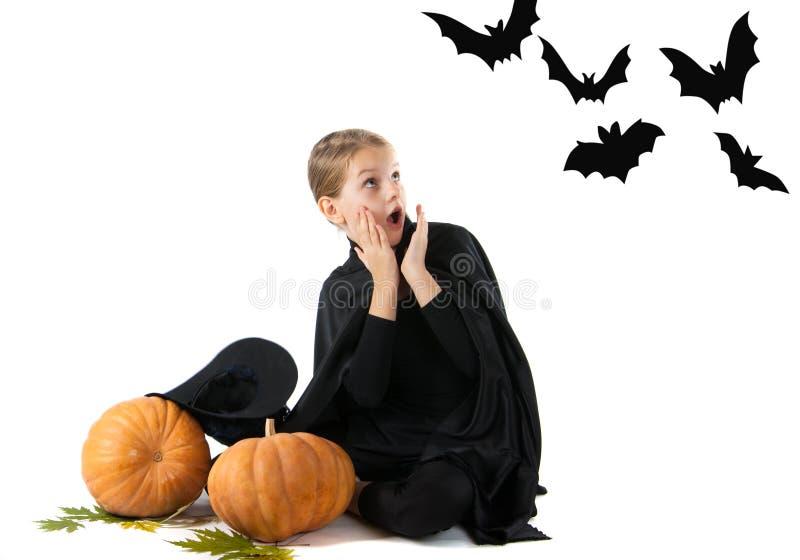 Halloween-Porträt des überraschten und erschrockenen Mädchens im Hexenkostüm stockbild