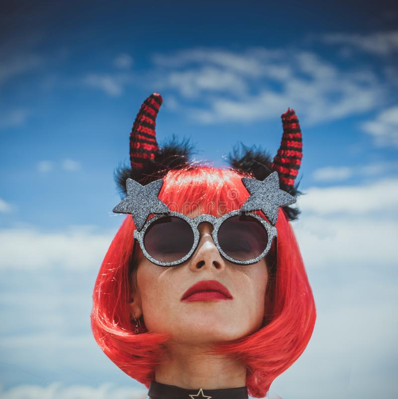Halloween. Portrait of a beautiful girl in a red wig with horns close-up against a blue sky. Red, holiday makeup. stock photos