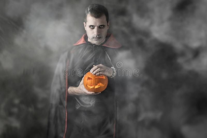 Halloween portrait Caucasian white man holding pumpkin dressed and makeup stylised for vampire on dark smoky background stock image