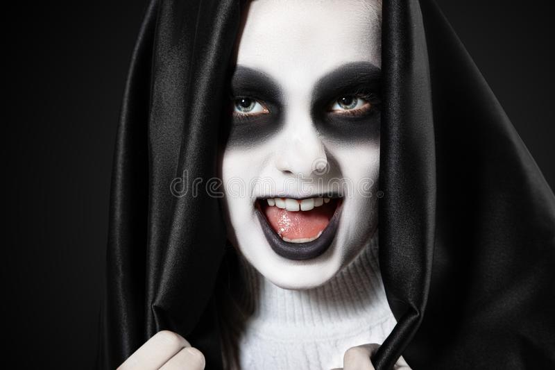 Halloween Portrait of a girl with makeup of a skeleton in a black hood stock images