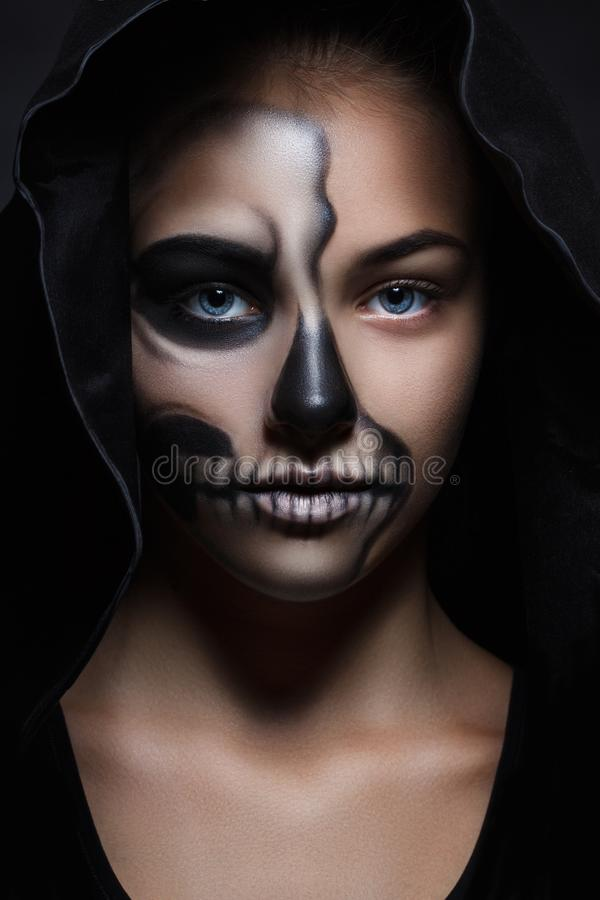Halloween portrait of young beautiful girl in a black hood. skeleton makeup stock photos