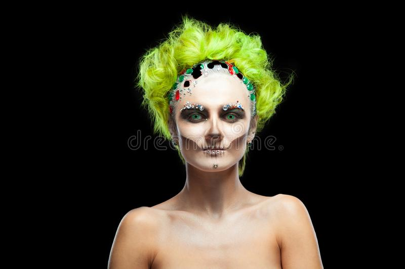 Halloween. Portrait of young beautiful girl with make-up skeleton on her face. And green hair. Isolated on black royalty free stock photography