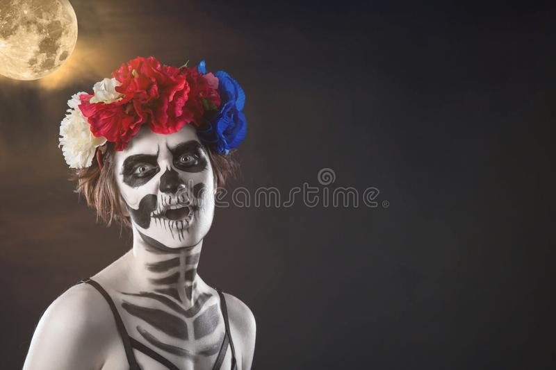 Halloween. Portrait of young beautiful girl with make-up skeleton on her face royalty free stock image