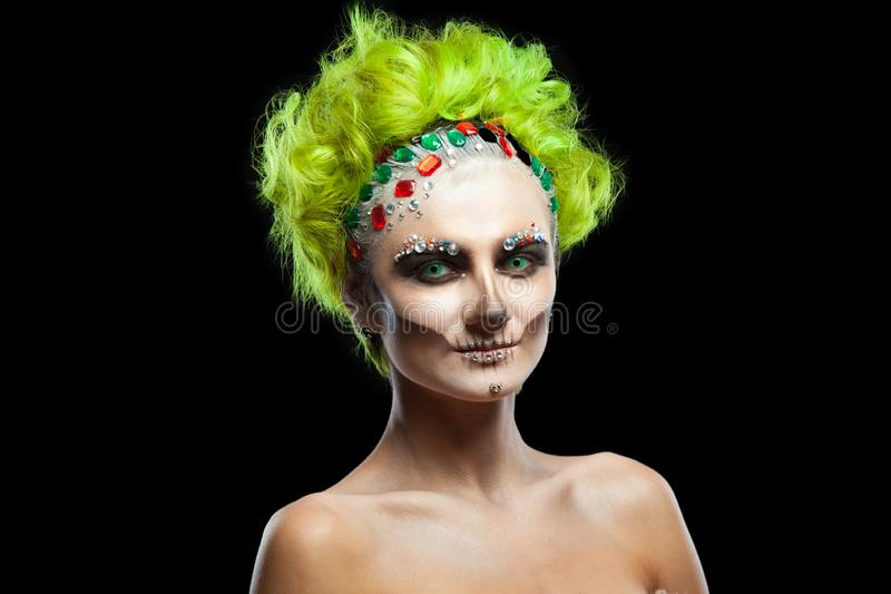 Halloween. Portrait of young beautiful girl with make-up skeleton on her face. And green hair. Isolated on black stock photo