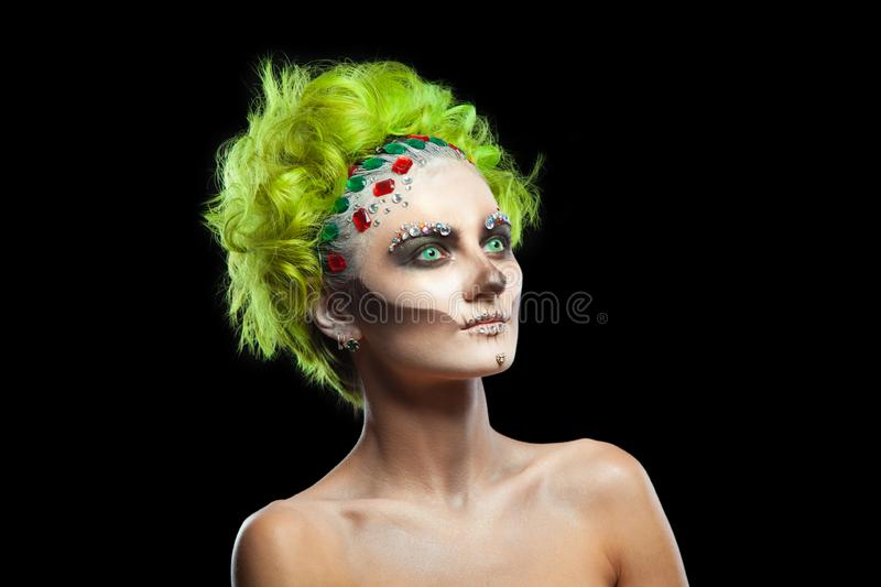 Halloween. Portrait of young beautiful girl with make-up skeleton on her face. And green hair. Isolated on black stock photography
