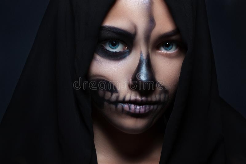 Halloween. Portrait of a young beautiful girl with skeleton makeup on her face. royalty free stock photo