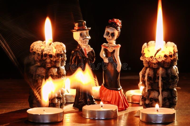 Halloween: postacie dwa kośca mężczyzna i kobieta przeciw tłu płonące świeczki w formie fotografia stock