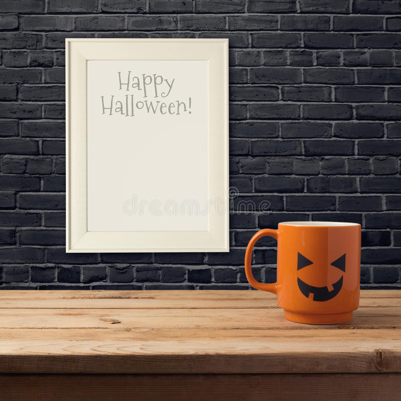 Halloween poster mock up template. Coffee cup as jack o lantern pumpkin on wooden table over black brick wall. Halloween holiday poster mock up template. Coffee royalty free stock photo