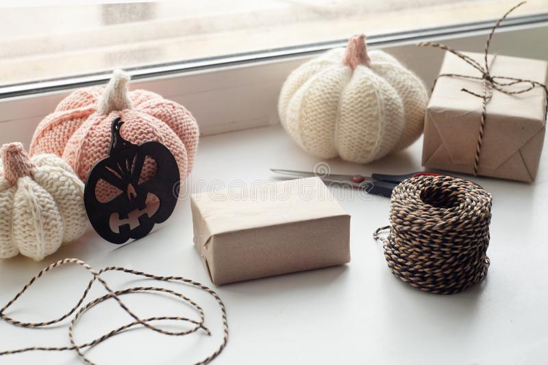 Halloween preparation. Craft halloween gift boxes on the window sill. Holidays, decoration and party concept - home room. With decorative pumpkin, halloween royalty free stock photo