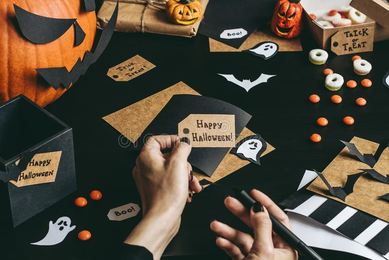 Halloween preparation. Hands making halloween cards using craft paper stock photos
