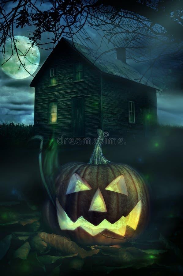 Halloween pumpa framme av ett spöklikt hus royaltyfri bild