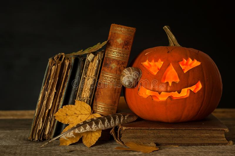 Halloween pumpkin and a book of spells. Carved pumpkin. Magic books. Traditional holiday. royalty free stock images