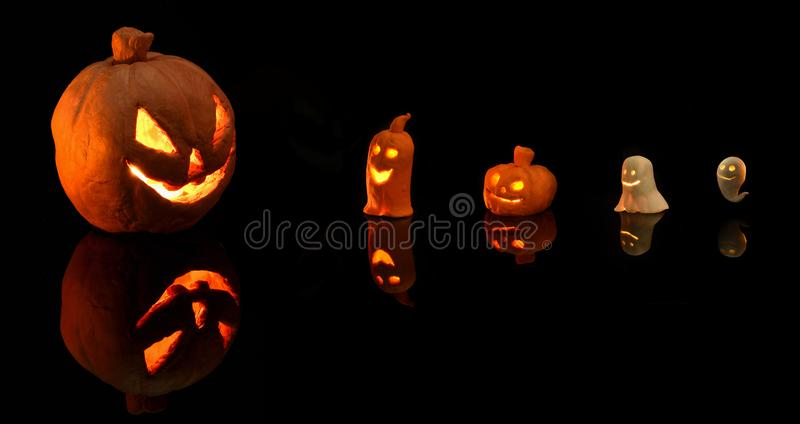 Halloween pumpkin with burning candles on black background stock images