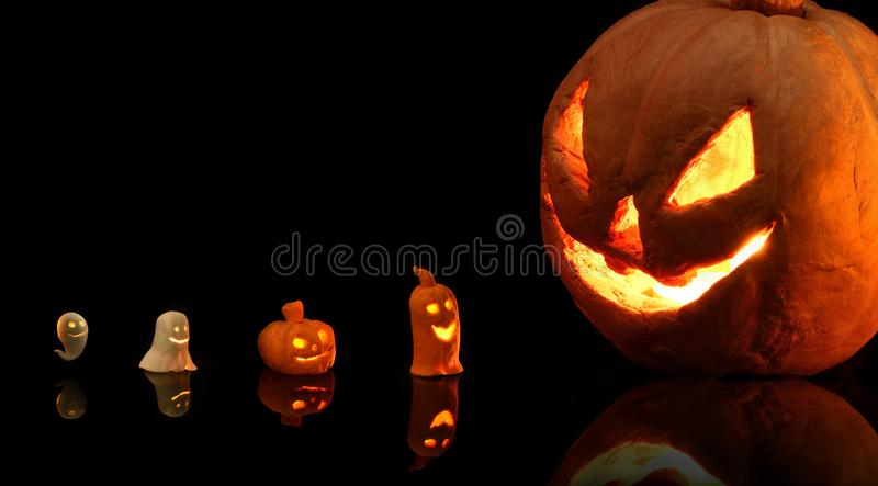 Halloween pumpkin with burning candles on black background royalty free stock images