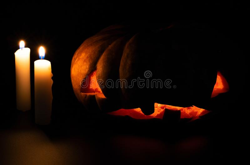 Halloween pumpkin and candle on dark background. Halloween party decor. Carved pumpkin with scary face and orange glow. royalty free stock image
