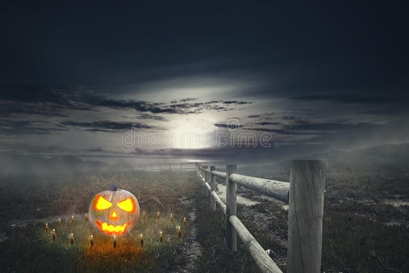 Halloween pumpkin with candle on the spooky grass field. Halloween background stock photo
