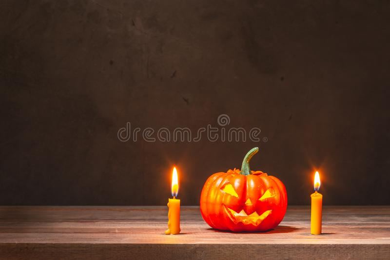 Halloween pumpkin and candles. Halloween pumpkin and yellow candles on wooden table royalty free stock images