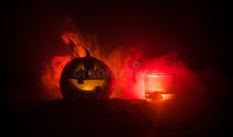 Halloween pumpkin with carved face and glass of whiskey with ice on a dark toned foggy background with zombies. Decorated. Selecti stock photos
