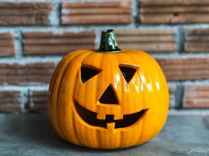 Halloween pumpkin on the cement floor with orange brick and dark light. royalty free stock image