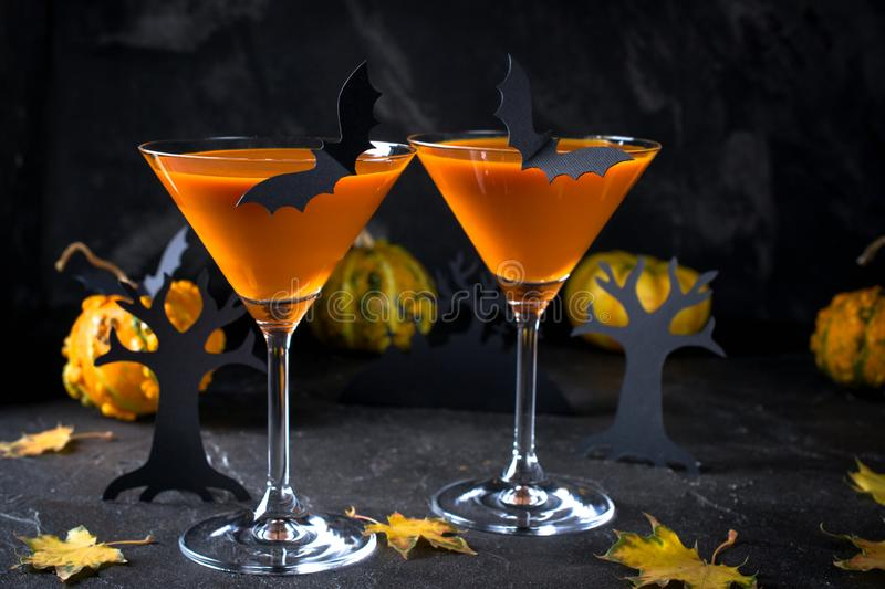 Halloween pumpkin cocktail. Food Concept, glasses with black bats and holiday decorations on dark background. Spooky royalty free stock photography