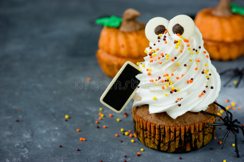 Halloween pumpkin cupcakes with funny meringue ghost, idea for H. Alloween party dessert selective focus stock image