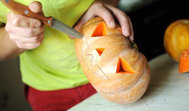 Halloween pumpkin cutting process, process of making Jack-o-lantern. Male hands with knife. Halloween pumpkin cutting process, process of making Jack-o-lantern stock photo