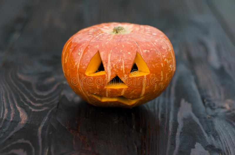 Halloween pumpkin on a dark wooden background. Jack O`Lantern head for a scary and all-out celebration. American tradition. Copy space royalty free stock photos