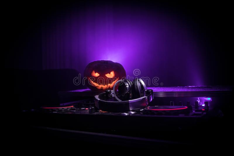 Halloween pumpkin on a dj table with headphones on dark background with copy space. Happy Halloween festival decorations and music. Concept. Empty space stock photography