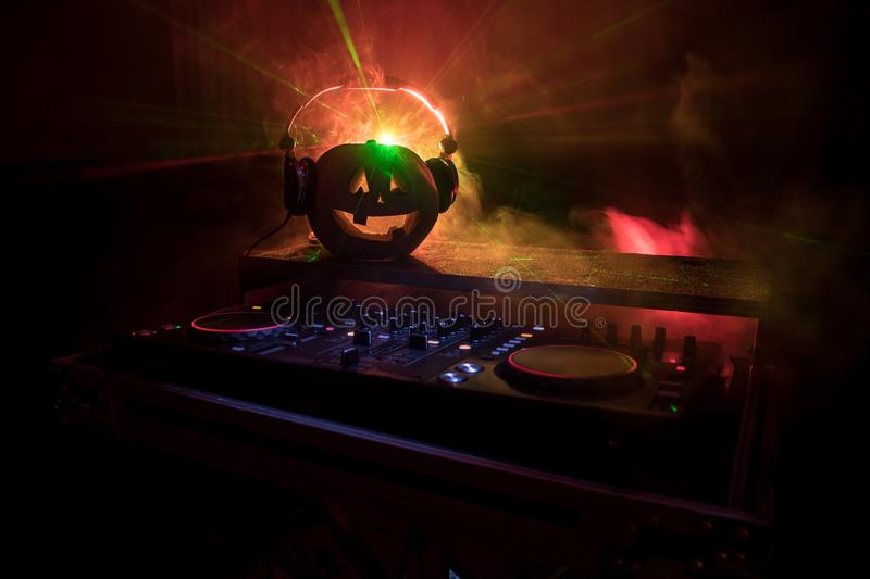 Halloween pumpkin on a dj table with headphones on dark background with copy space. Happy Halloween festival decorations and music. Concept. Empty space stock photos