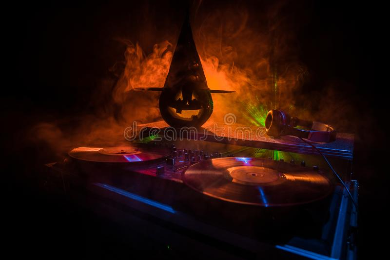 Halloween pumpkin on a dj table with headphones on dark background with copy space. Happy Halloween festival decorations and music. Concept. Empty space royalty free stock images
