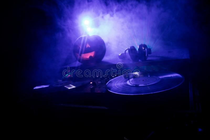 Halloween pumpkin on a dj table with headphones on dark background with copy space. Happy Halloween festival decorations and music. Concept. Empty space royalty free stock image
