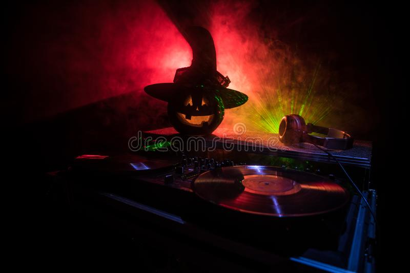 Halloween pumpkin on a dj table with headphones on dark background with copy space. Happy Halloween festival decorations and music. Concept. Empty space stock images
