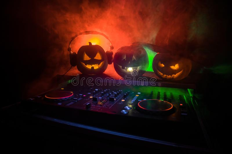 Halloween pumpkin on a dj table with headphones on dark background with copy space. Happy Halloween festival decorations and music. Concept. Empty space royalty free stock photo