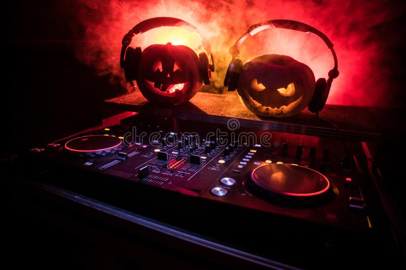 Halloween pumpkin on a dj table with headphones on dark background with copy space. Happy Halloween festival decorations and music. Concept. Empty space royalty free stock photography