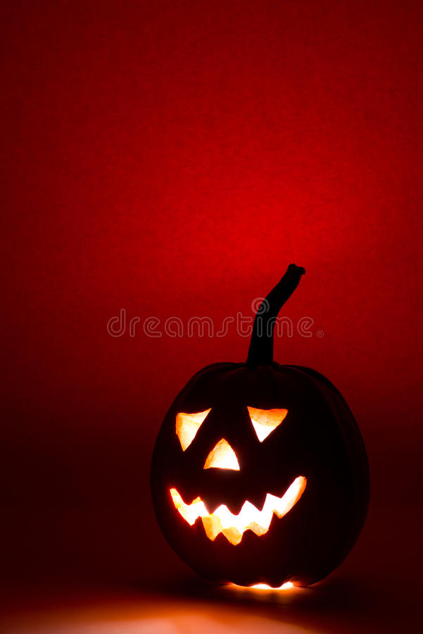 Halloween pumpkin, funny face on red background royalty free stock image