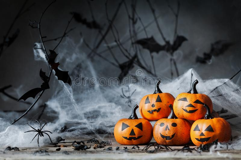 Halloween pumpkin with funny smile and spooky decoration on dark wood. royalty free stock image