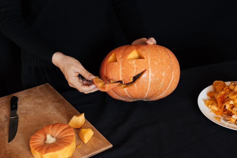 Halloween pumpkin. Girl hands prepares traditional decoration for the celebration royalty free stock photography