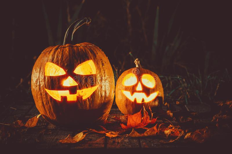 Halloween pumpkin with glowing face on a wooden background in a spooky forest night stock photos