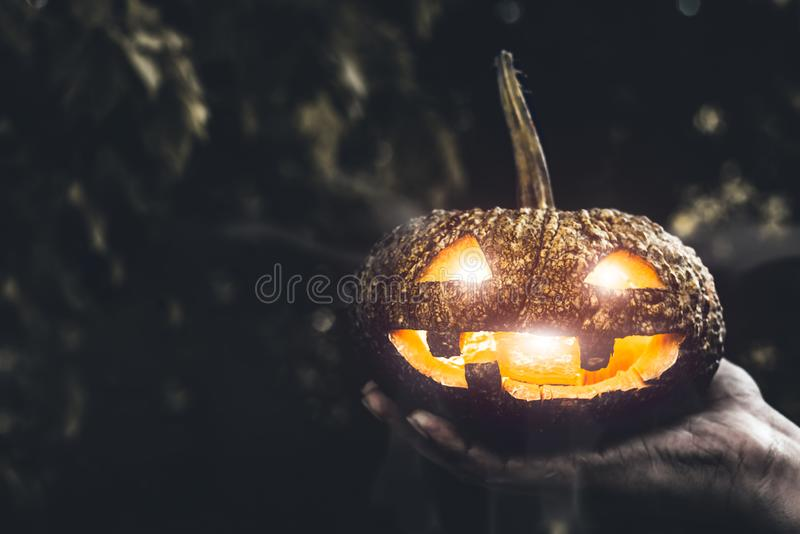 Halloween pumpkin in hand. Holiday and Religion concept. Ghost in pumpkin theme. Witchcraft and mystery spell theme.  stock image