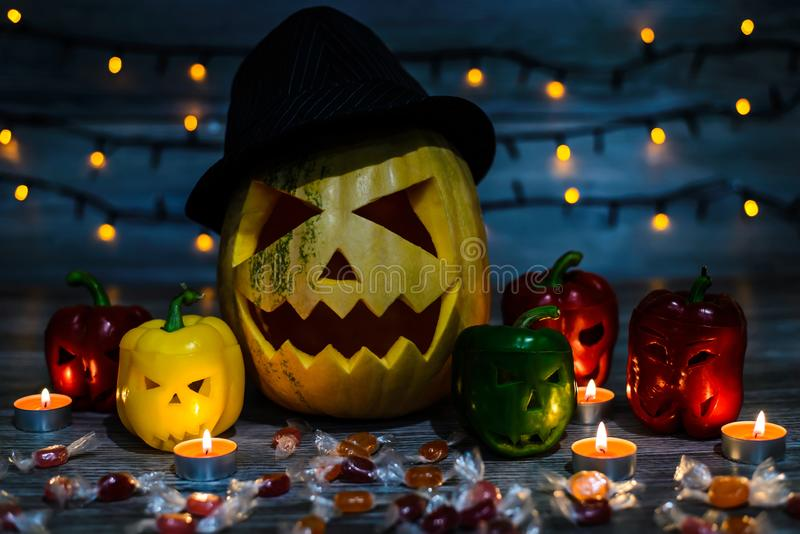 Halloween pumpkin in hat with terrible face surrounded by pepper stock image