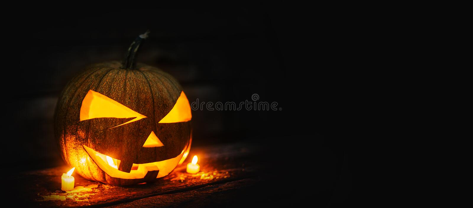 Halloween pumpkin head jack lantern with burning candles on dark moody background. Halloween concept with copy space for your design stock images