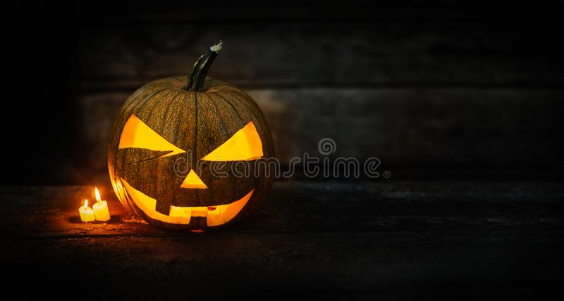 Halloween pumpkin head jack lantern with burning candles on dark moody background. Halloween concept with copy space for your design royalty free stock image