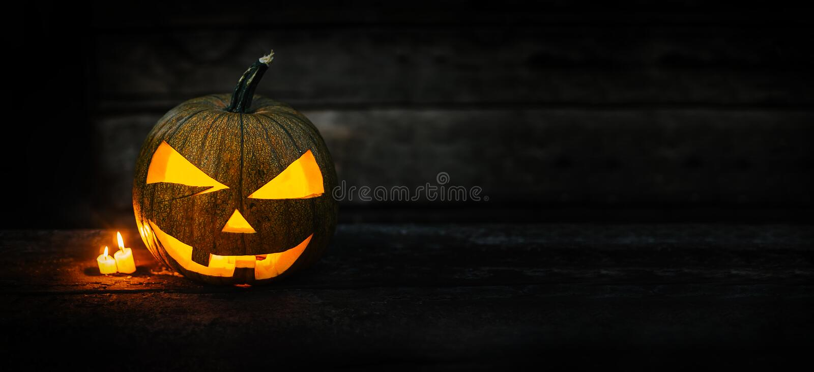 Halloween pumpkin head jack lantern with burning candles on dark moody background. Halloween concept with copy space for your design stock image