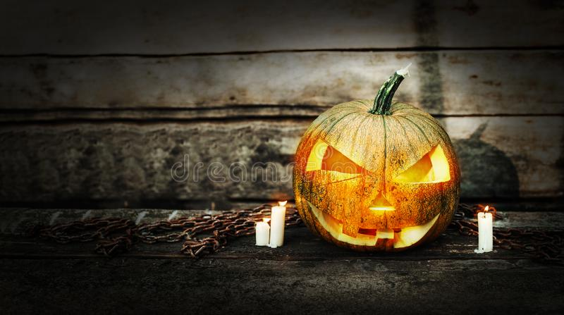 Halloween pumpkin head jack lantern with burning candles on dark moody background. Halloween concept with copy space for your design stock photo