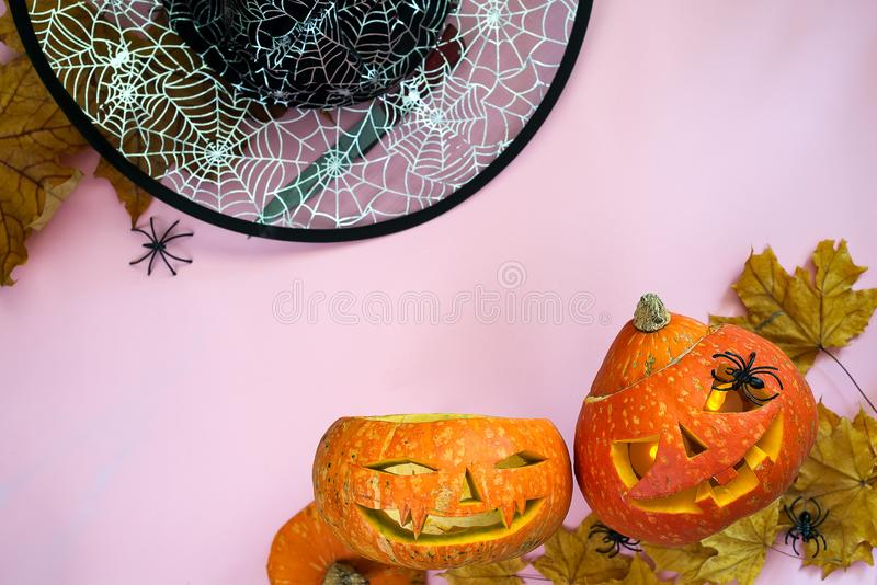 Halloween pumpkin head jack lantern frame with burning candles, witch hat and spider isolated on orange, flat lay with royalty free stock photography