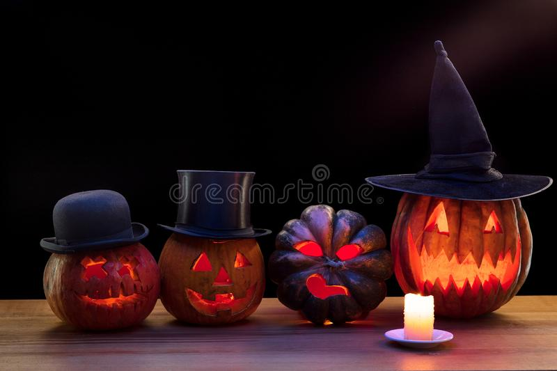 Halloween pumpkin head jack lantern with scary evil faces and candles. Halloween pumpkin head jack-o-lantern in hats with scary evil faces and candles. Seasonal stock images