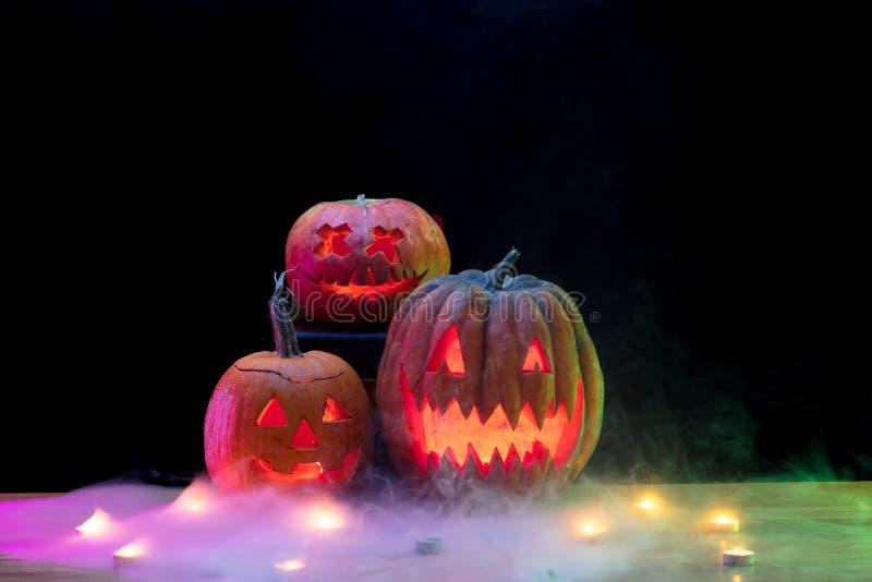 Halloween pumpkin head jack lantern with scary evil faces. Halloween pumpkin head jack-o-lantern with scary evil faces and candles. Seasonal illuminated stock photo